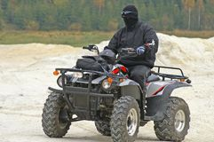 ATV rider with black mask. Cruising on dirt track Royalty Free Stock Image