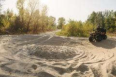 Atv rider in helmet climbing sandy road in forest royalty free stock images