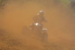 ATV rider in helmet riding in dust. Royalty Free Stock Images