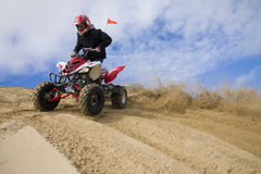 ATV rider spray sand in dunes. Close up of ATV rider spinning tires in sand, making a rooster tail. Wide Angle, good copy space Stock Photography