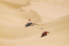 ATV riders in the vast desert. Couple of ATV riders kicking off sand in vast california desert Royalty Free Stock Photography