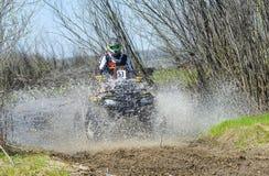 ATV rides through the mud with a big splash Stock Image