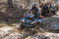 ATV rides through the mud with a big splash Royalty Free Stock Images