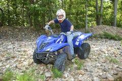 ATV Riding. A teenager riding an ATV by a river Stock Photos