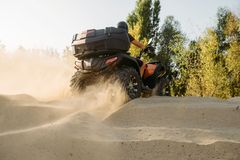 Atv riding in sand quarry, dust clouds, quad bike stock photography
