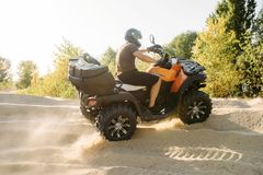 Atv riding in sand quarry, dust clouds, quad bike royalty free stock images