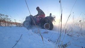 ATV riding in the snow backlight speed slow shooting stock footage