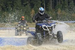 ATV splashing. ATV racer driving through a pit filled with water, chased by a quad Stock Photos