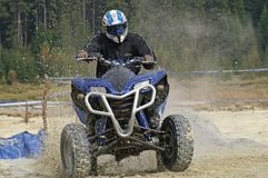 ATV splashing mud. ATV racer driving through a pit filled with water Stock Image