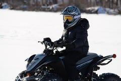 ATVing在冬天在一个大风天 免版税库存照片