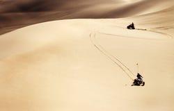 ATVs conduisant par des dunes de sable de désert Photo stock