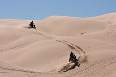 ATVs hopping the dunes. Two ATVs wind their way, racing up the hilly Dunes in Californias Imperial Sand Dunes Royalty Free Stock Images