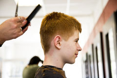 Atyoung boy with red hair getting a haircut Royalty Free Stock Photo