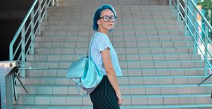 Atypical beauty attractive blue-haired girl. With a backpack of silver fabric plans on the background of steps stock images