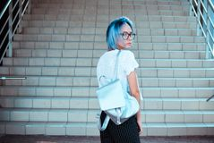 Atypical beauty attractive blue-haired girl. With a backpack of silver fabric plans on the background of steps royalty free stock photos