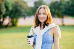 Außenaufnahme der angenehmen schauenden jungen europäischen Frau mit dem dunklen Haar, Griffmitnehmerkaffee, verbringt Freizeit i lizenzfreie stockfotografie