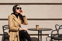 Außenaufnahme der brunette Frau modernen Mantel, schwarze Ausstattung und Sonnenbrille tragend, sitzend an der Restaurantterrasse lizenzfreie stockbilder