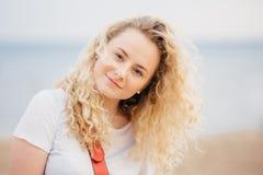 Außenaufnahme der gelockten schönen jungen Frau mit frischer Haut, Blicke positiv an der Kamera, trägt zufälliges weißes T-Shirt, lizenzfreies stockfoto