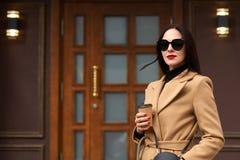Außenaufnahme der schönen jungen stilvollen brunette Frau, die den beige Mantel aufwirft im Freilicht, Wege entlang den Stadtstra stockfotos