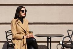 Außenaufnahme der stilvollen Frau modernen beige Mantel tragend, Bruch Café der Straße habend im im Freien und Heißgetränk trinke lizenzfreie stockfotografie
