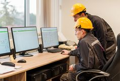 Außendienstingenieure kontrollieren RelaisSchutzsystem mit Schoss Lizenzfreie Stockfotos