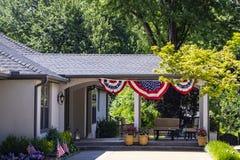 Außerhalb des bedeckten Patios mit Möbeln und patriotisch weiter von Juli-Flagge und der amerikanischen Flaggen fest im Blumenbee stockfoto