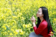 Au beau premier ressort, un support de jeune femme au milieu des fleurs jaunes class?es pour sentir des fleurs de Cole photos stock
