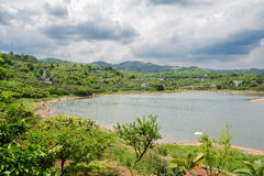 Au bord du lac verdoyant en ressort nuageux Photographie stock libre de droits