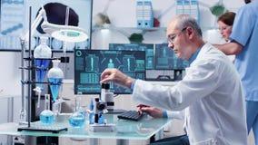Au centre de recherche occupé le scientifique mûr analyse des échantillons provenant des tubes banque de vidéos