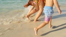 Au coucher du soleil, à la maman heureuse, au papa et au bébé de famille fonctionnement nu-pieds sur le sable humide ressac de me banque de vidéos