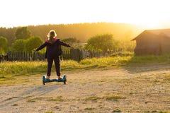 Au coucher du soleil, une fille de l'adolescence monte un hoverboard photos libres de droits