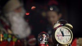 Au crépuscule de la nuit, dans le premier plan est un réveil, à l'arrière-plan Santa Claus étreint une petite fille mignonne banque de vidéos