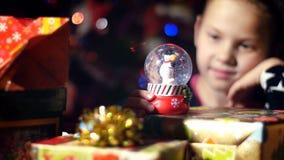 Au crépuscule de la nuit, parmi les cadeaux en paquets de papier colorés lumineux, une fille blonde assez petite avec un rose banque de vidéos