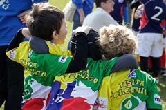 Au-dessous de 12 rugbys les joueurs étreignent ensemble après le match fini Photo libre de droits