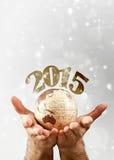 2015 au-dessus de la prise de la terre de globe par des mains du ` s de l'homme Images stock