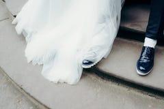 Au-dessus de la vue aux jambes de nouveaux mariés sur les escaliers Regardez de la robe de mariage de kong des chaussures de jeun Photos stock