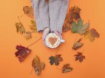 Au-dessus de la vue aux mains tenant la tasse de cappuccino avec la forme de coeur Image libre de droits