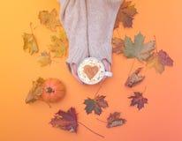 Au-dessus de la vue aux mains tenant la tasse de cappuccino avec la forme de coeur Photo stock