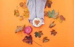 Au-dessus de la vue aux mains tenant la tasse de cappuccino avec la forme de coeur Images stock