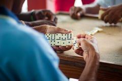 Au-dessus de la vue d'épaule des dominos dans des mains du ` s d'homme d'afro-américain Image stock