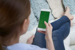Au-dessus de la vue d'?paule de la femme se trouvant au t?l?phone de Sofa Using Green Screen Mobile ? la maison images stock