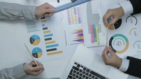 Au-dessus de la vue de deux hommes d'affaires travaillant ensemble au bureau discutant le budget, diagrammes financiers clips vidéos