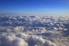 Au-dessus de la vue lumineuse de paysage de cumulus de la fenêtre d'un avion images stock