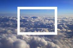 Au-dessus de la vue lumineuse de paysage de cumulus de la fenêtre d'un avion avec un cadre blanc image stock