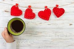Au-dessus de la vue de la main femelle tenant la tasse de café chaude avec le coeur rouge sur la table en bois Photo dans le styl Images stock