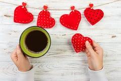 Au-dessus de la vue de la main femelle tenant la tasse de café chaude avec le coeur rouge sur la table en bois Photo dans le styl Photo libre de droits