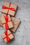Au-dessus du boîte-cadeau brun et du ruban rouge avec l'étiquette sur le fond en bois avec l'espace vertical Images libres de droits