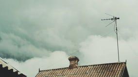 Au-dessus du dessus de toit les nuages flottent banque de vidéos