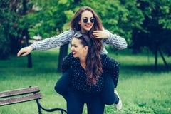 Au?enaufnahme der jungen Frau ihre Freundin auf ihr zur?ck tragend lizenzfreie stockbilder