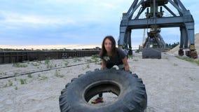Au lever de soleil, une jeune femme sportive exécute des exercices utilisant une grande roue lourde de tracteur, donne des leçons banque de vidéos